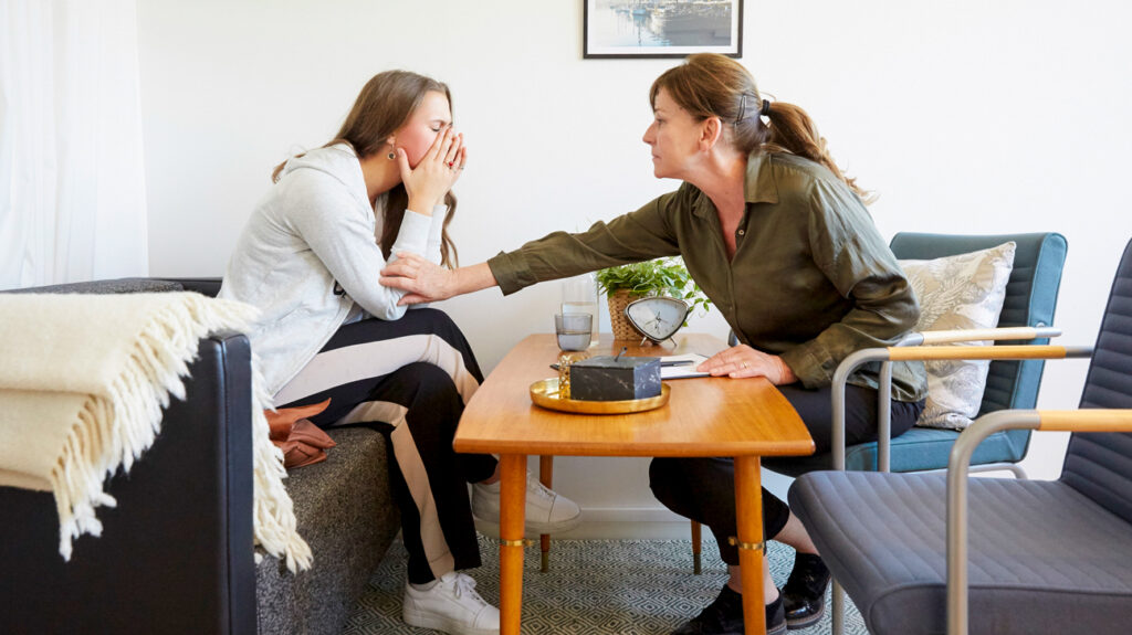 Therapist consoling teenage patient during the session. therapy without insurance.