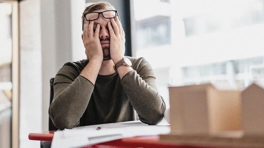 一个男人抱着他的脸,因为他在工作中的压力疼痛和胃痛