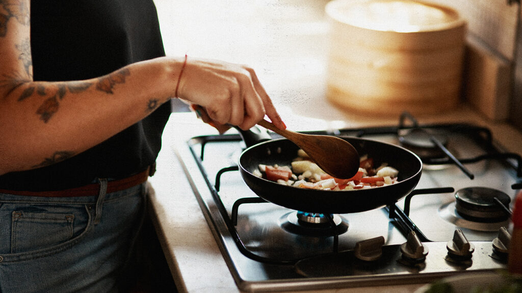 A person with a tattooed arm is using a frying pan to prepare a healthy recipe for weight loss.