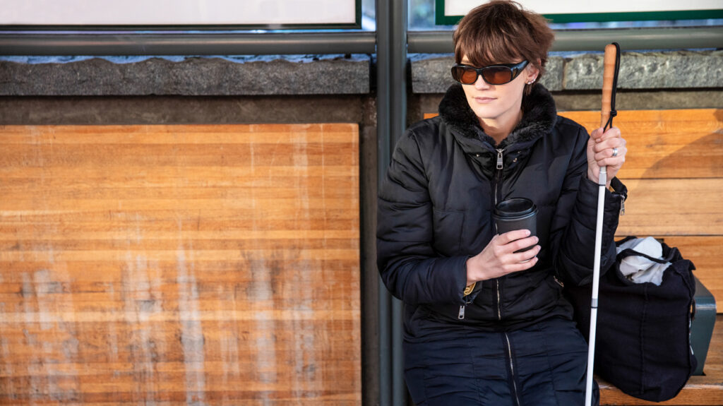 woman legally blind with a stick waiting at bus stop