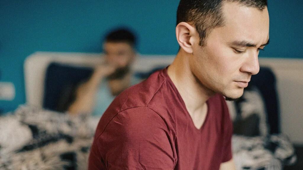 Un homme assis sur un lit à l'air déçu alors qu'il essaie de comprendre comment faire face à la dysfonction érectile dans un mariage