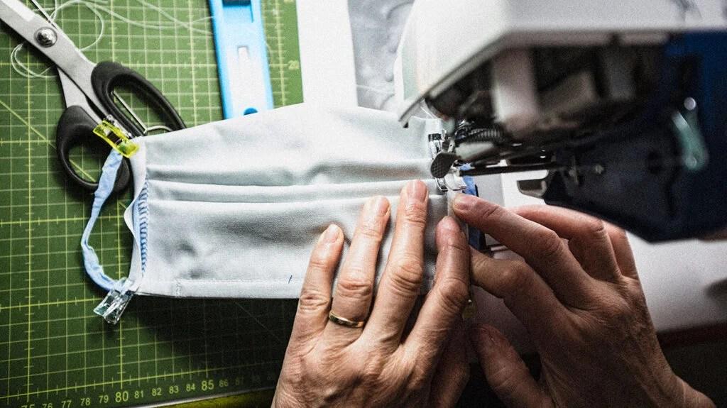Une personne fabrique un masque facial dans cette image pour accompagner un article sur la proposition d'un test bon marché et accessible pour l'efficacité du masque.