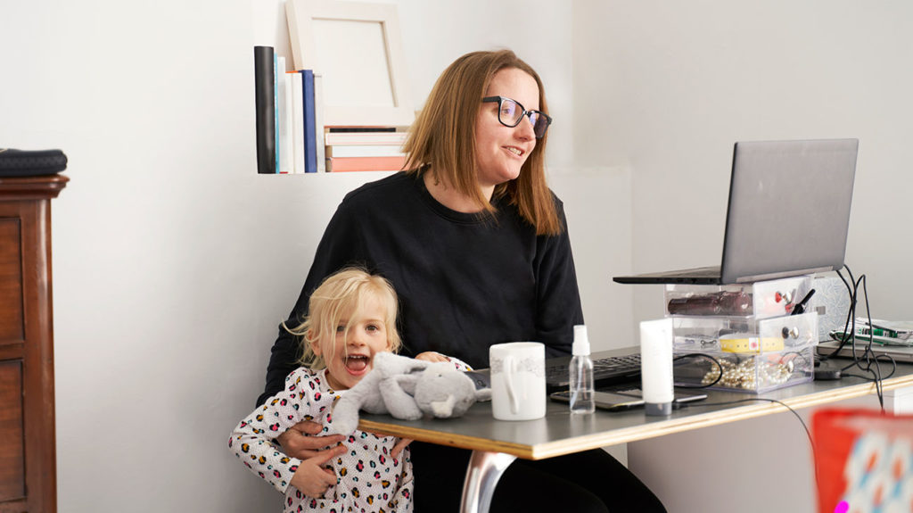 A mother in the United Kingdom seen on a conference call while attending to her toddler in order to illustrate mental health effects of COVID-19.