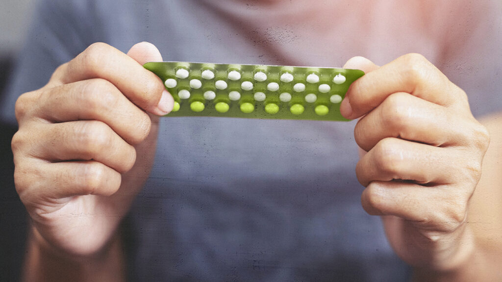 A photo of a woman holding a blister pack of birth control pills to accompany the article 10 most common birth control pill side effects