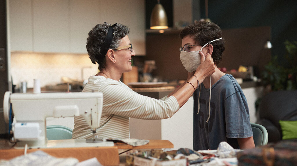 "A photo of a mother fitting a face mask to her son to accompany the article ""Is COVID-19 more dangerous because it reduces specific microRNAs?"""