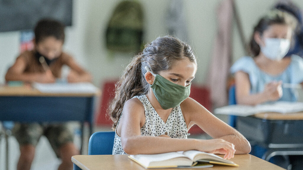 "A photo of elementary aged children wearing masks in a classroom to accompany the article, ""COVID-19: children have a higher viral load than adults."""