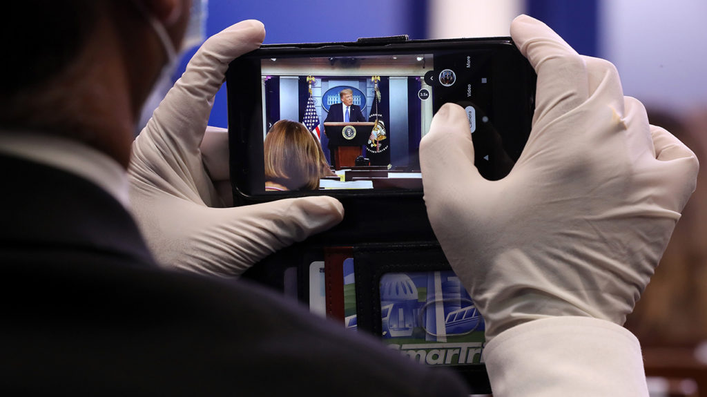 A journalist wears latex gloves to protect against the coronavirus while taking photos of U.S. President Donald Trump during a news conference about his administration's response to the ongoing pandemic in the Brady Press Briefing Room at the White House July 22, 2020 in Washington, DC. This is the second briefing the president has given in as many days. Poll numbers about his handling of COVID-19 have been falling as cases of deadly virus have spiked across the country