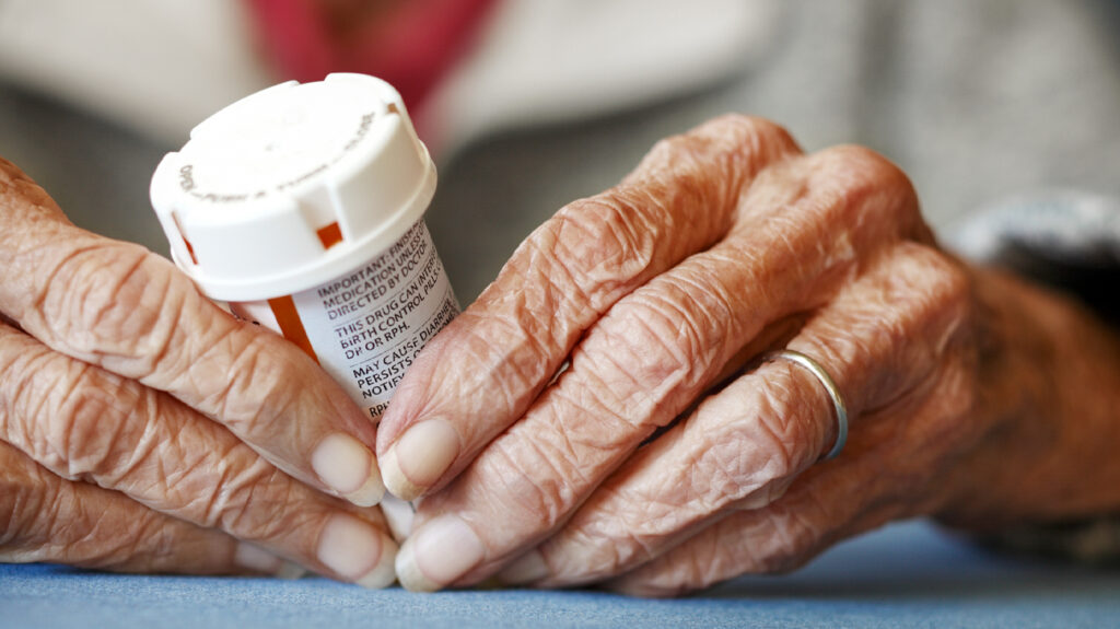A closeup of the hands of an older female adult holding a prescription pill pot as part of Medicare generic tier medication