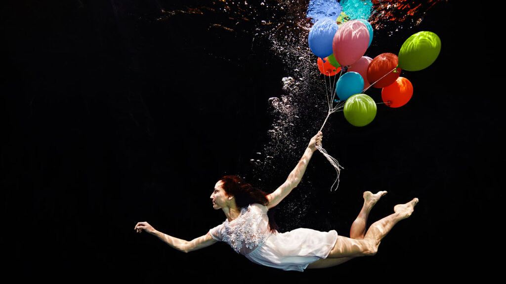 A woman swims with balloons underwater to illustrate lucid dreaming.