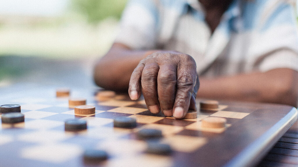 "A senior Black man, whose face is not shown, players checkers to accompany the article, ""Dementia is often overlooked as a cause of death"""