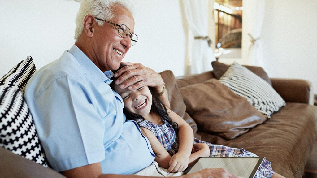 A senior man sits on the couch with his granddaughter and thinks about how to choose a medicare advantage plan.