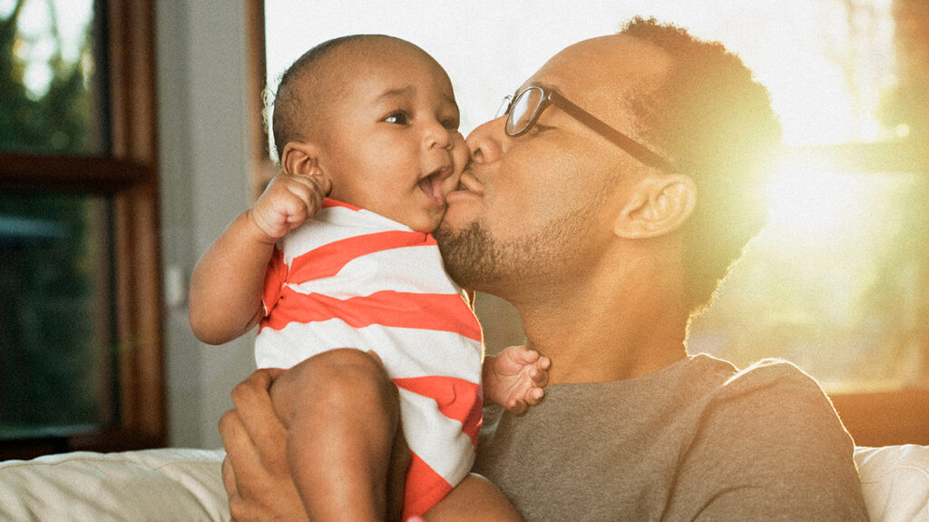 A photograph of a man kissing a baby to accompany an article on babies shaking their heads.