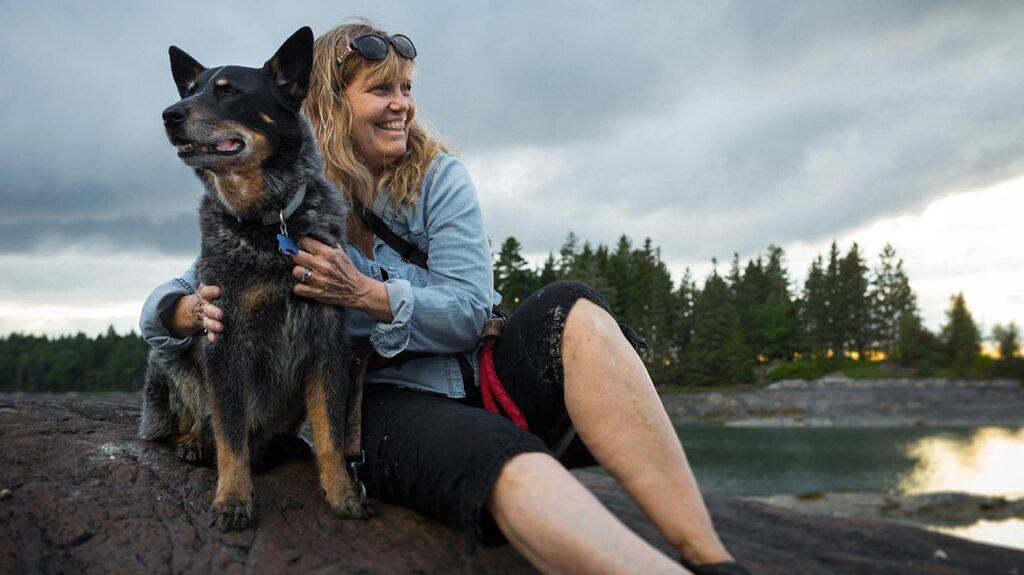 A woman with harvard pilgrim medicare relaxes with her dog in Maine.
