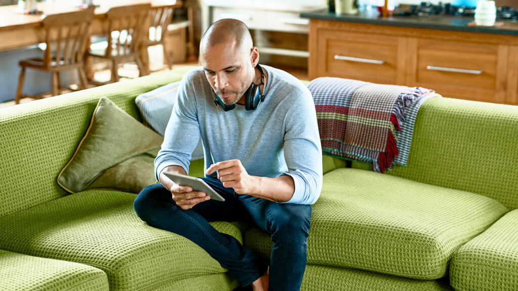man sitting searching for free mental health on digital tablet