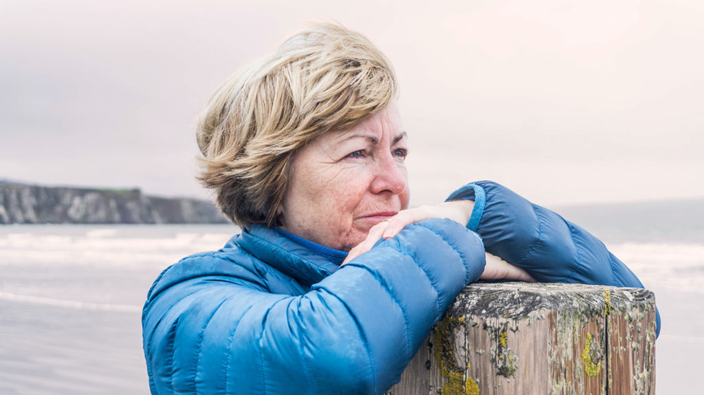 a woman looks pensively into the distance while standing on a beach
