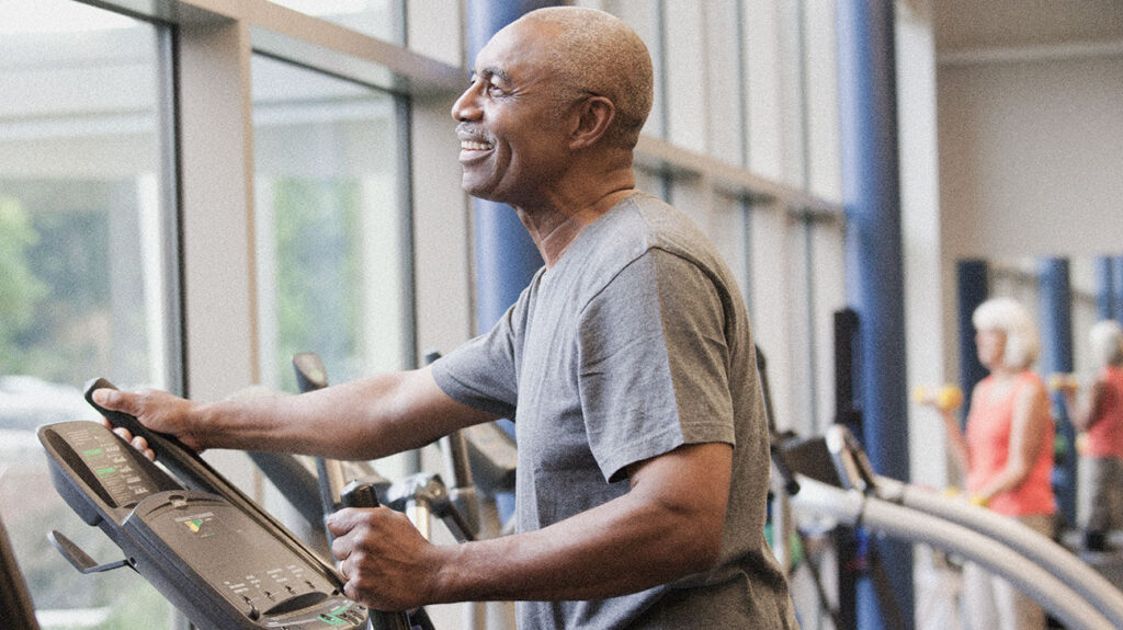 A male senior exercises on an elliptical to accompany the article Immune aging and how to combat it.