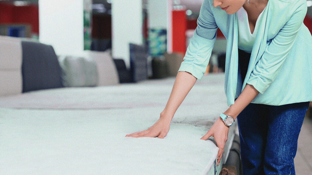 A person inspects a mattress as they decide between purchasing a memory foam or latex mattress.