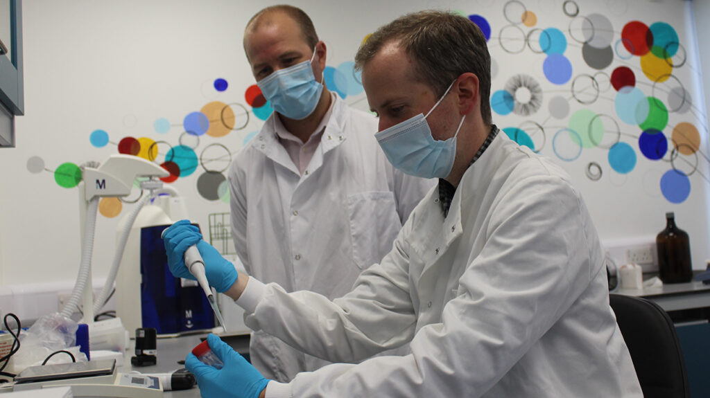 James Hindley, Ph.D working with another scientist in a lab