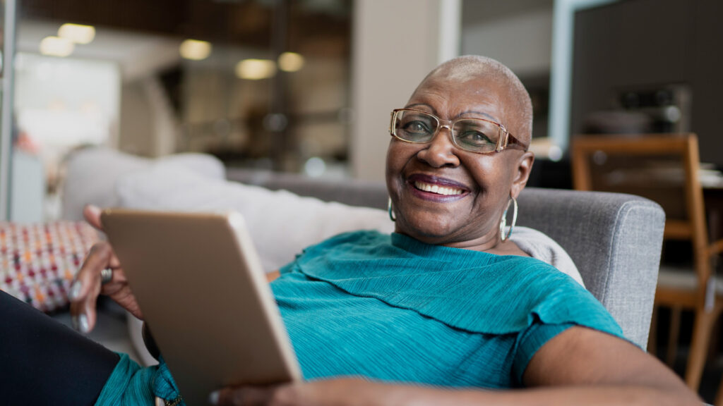 Older black female adult holding a tablet device and looking relaxed and happy about medicare easy pay