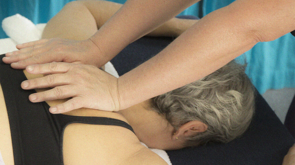 A person receives a deep tissue massage to their upper back.