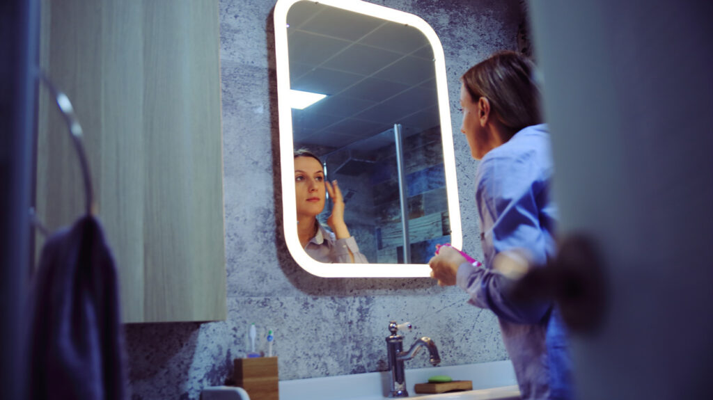 A woman looking at her skin in a bathroom mirror to find out what type of skin she has.