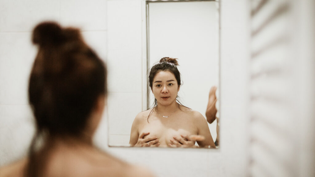 A woman looking in the mirror and examining their breasts for bumps on nipples.