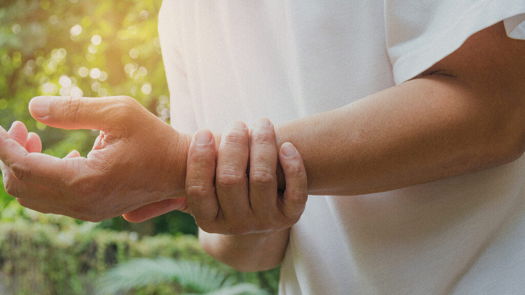 "A person holds their wrist which has arthritis to accompany the article, ""Antibody-based arthritis drug could treat severe COVID-19"""