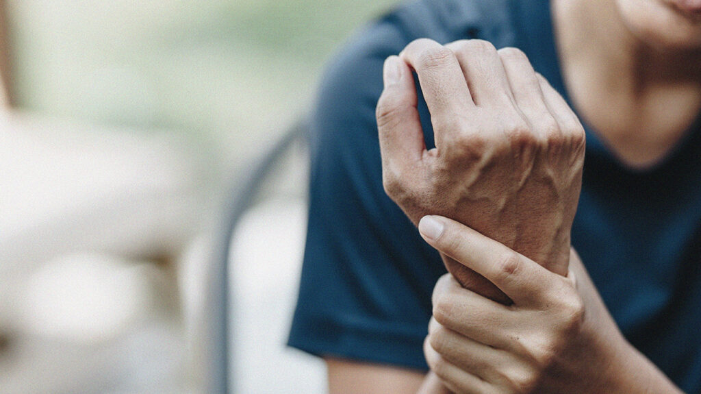 A person holding their wrist, due to joint pain.