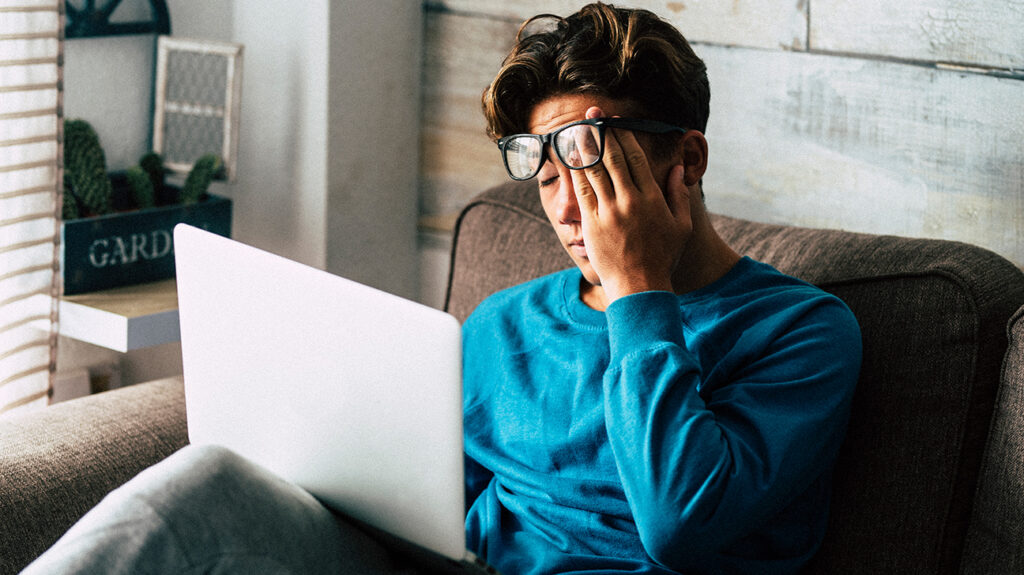 Man struggling with computer eye strain.