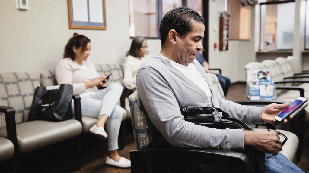 a man sat in a doctors waiting room looking at his phone