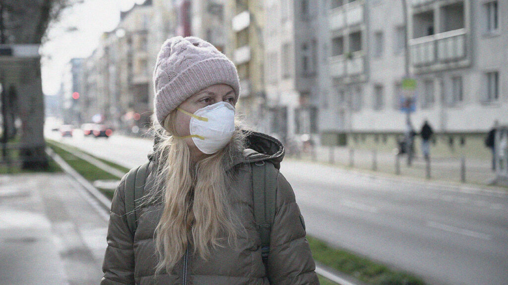pessoa usando máscara facial no tempo frio