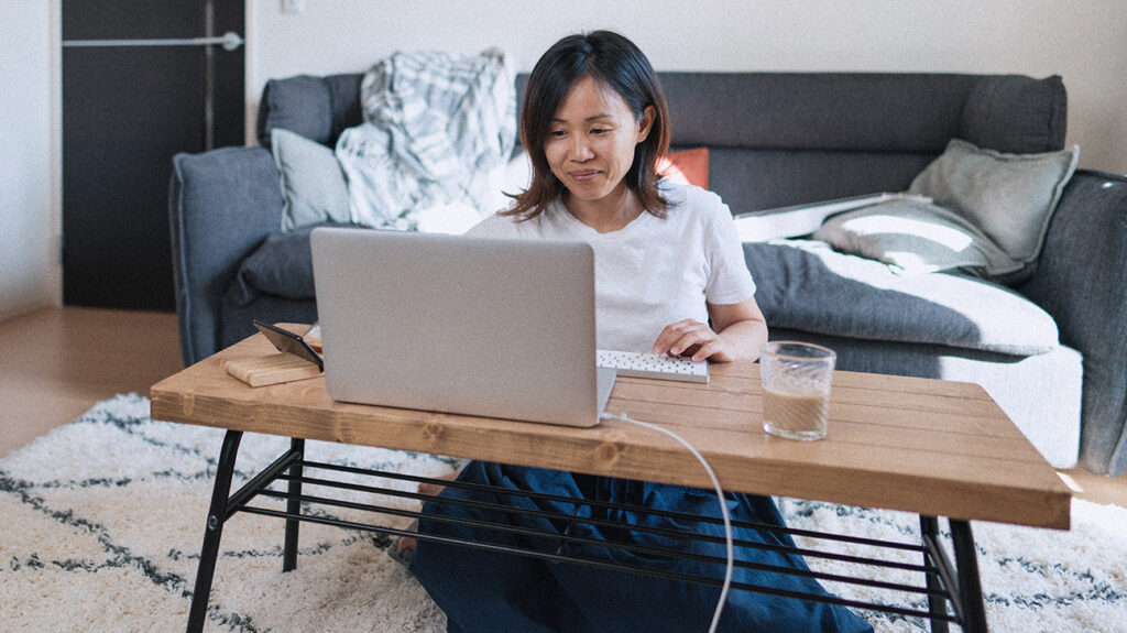 A person using a laptop to receive online grief therapy while at home.