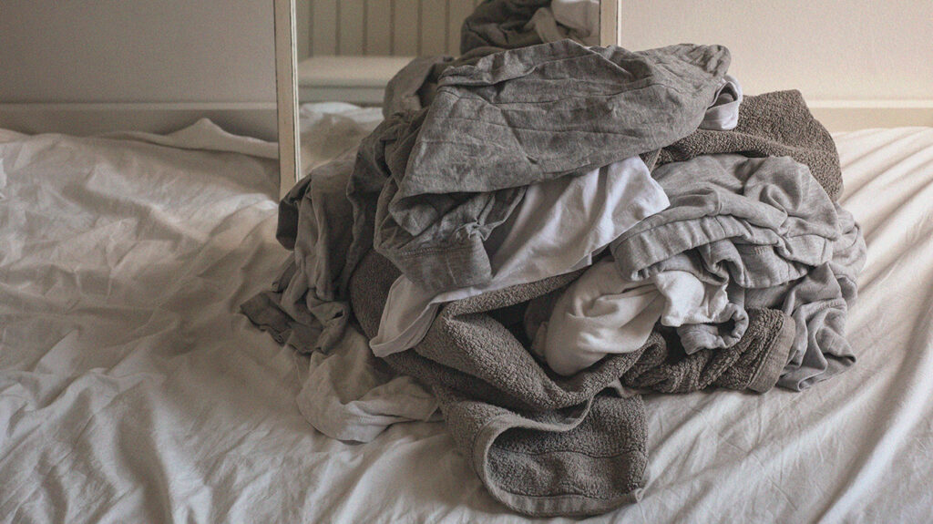 A pile of bed sheets on a bed. A person is preparing to clean the bed sheets after having anal sex.