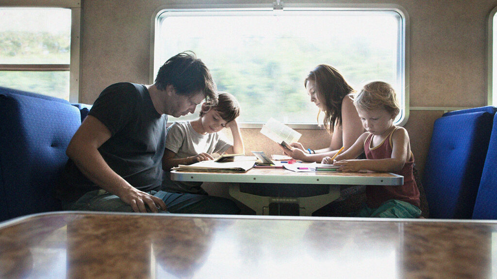 Family reading together on a train