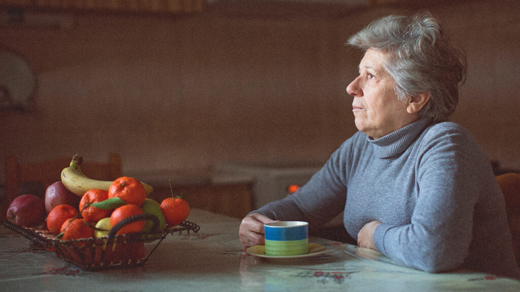 older woman looking lonely sitting at table