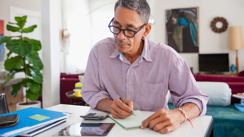 man working on personal finances at home thinking about medicare income limits