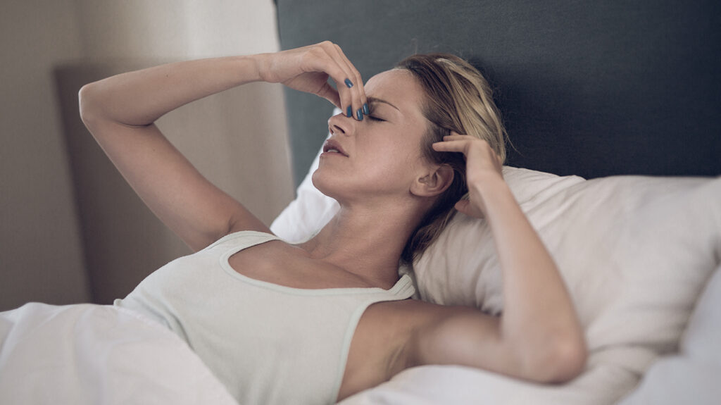 A person laying in bed feeling unwell. Perhaps they have concerns about having an STI and worrying about how long it will be before STI symptoms show and thinking when they should get tested.