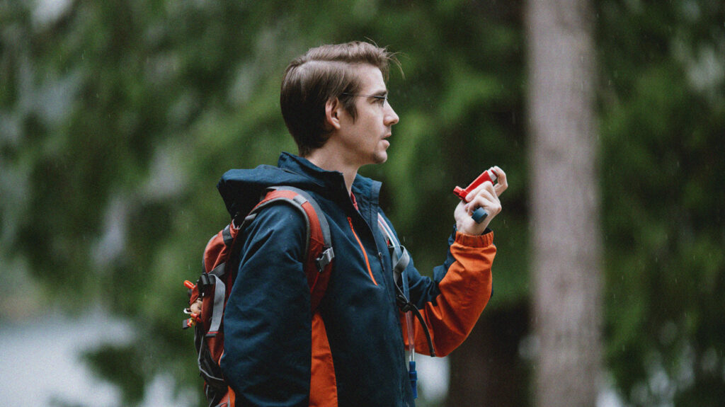 a person hiking in the woods uses a fluticasone propionate inhaler