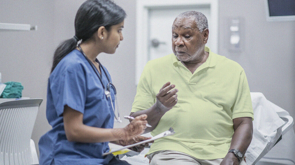 Older Male Adult Patient Talking with Female Doctor who is delivery patient-focused care following MACRA Medicare implementation
