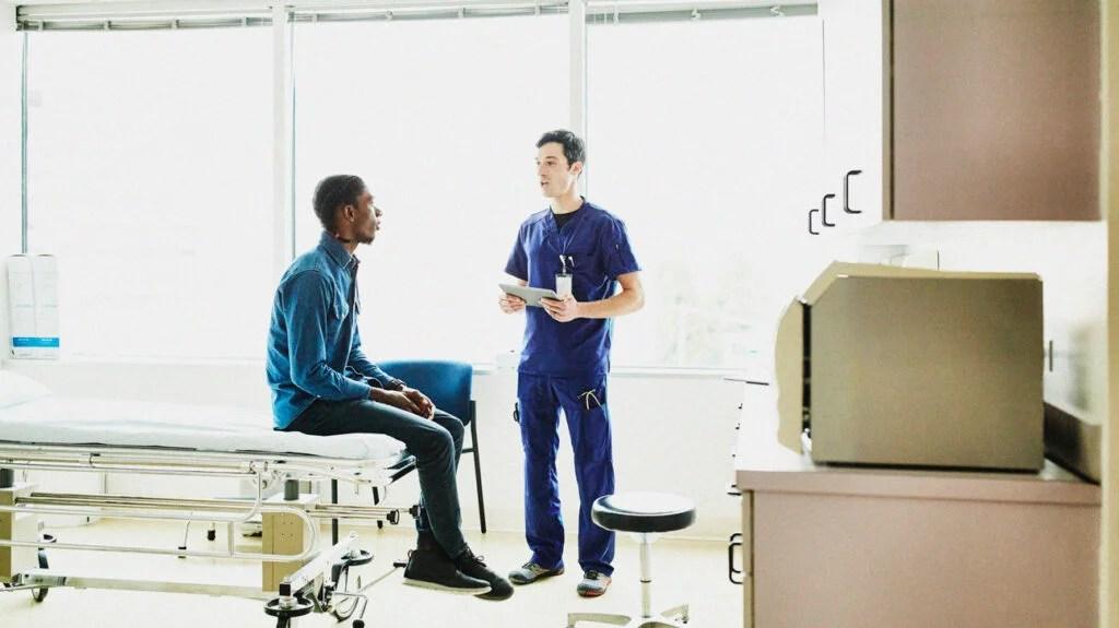 Homem sentado na cama em um quarto de hospital fala com um médico sobre eczema peniano.