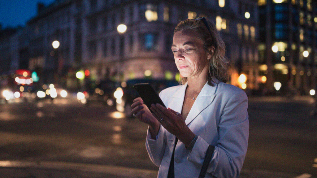 Older white female adult looking at cell phone screen which is lighting up her face as she is in a city in the evening and there are street and traffic lights around her. She could be researching when the Medigap open enrollment period is.
