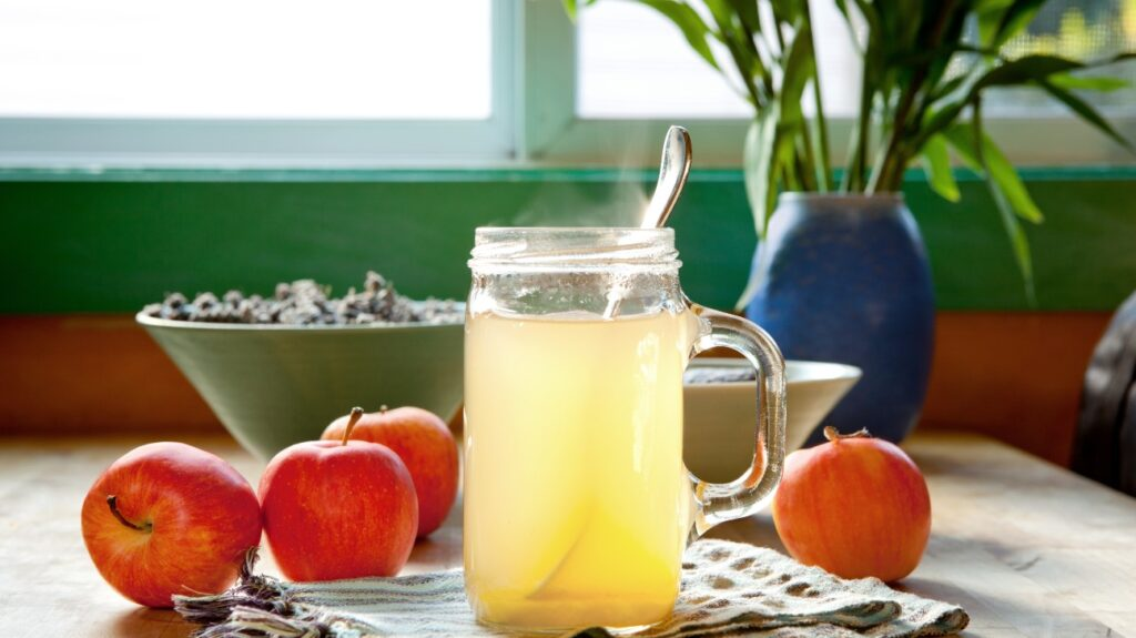 A yellow drink in a jar, plus some fruit, for preventing a cold.