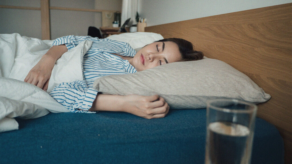 A person wearing blue and white striped pijamas lying in bed.