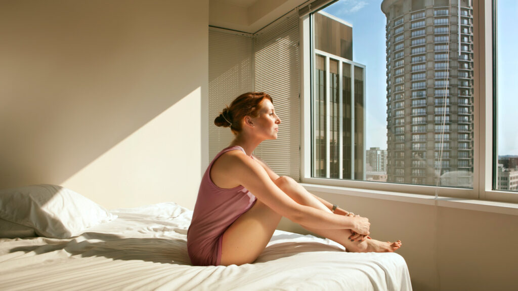 Woman sitting on her bed looking out across the city