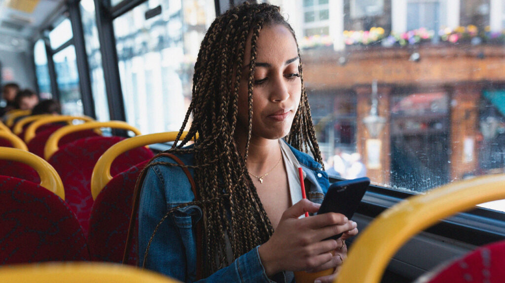 Pregnant woman thoughtfully checks phone on bus.