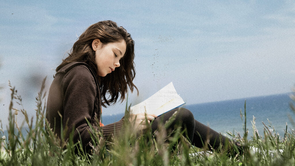 A girl sits and writes poetry on a hillside for therapy purposes.