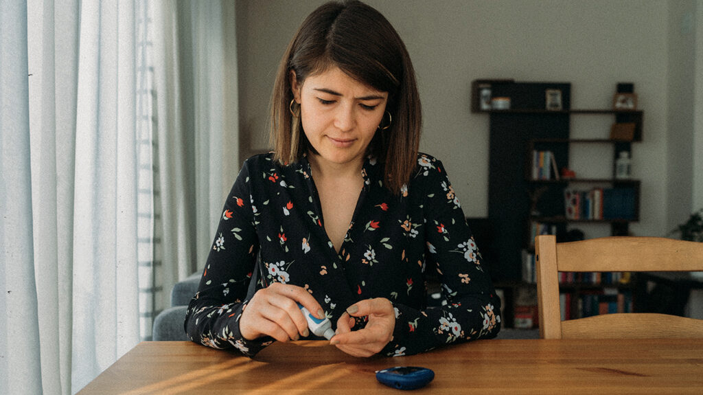 A woman with diabetes checks her blood sugar in an image accompanying the article COVID-19 and preexisting conditions: Is a holistic approach needed?
