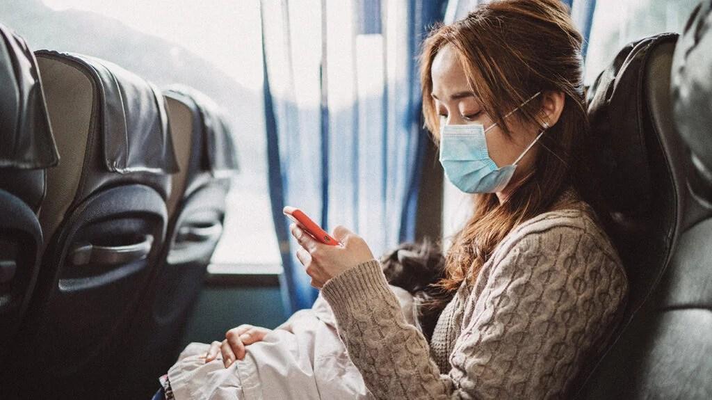 公车上戴着面具看手机的女人