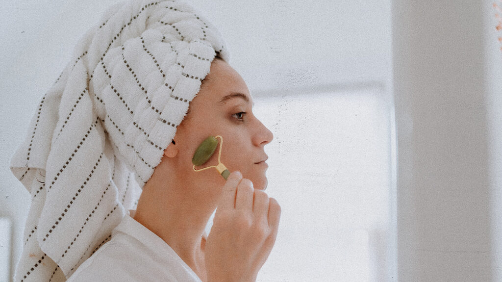 A woman with her hair wrapped in a towel, using a jade face roller for its skin care benefits.