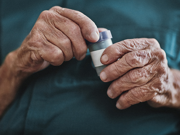 close up of an old woman's hands opening pills